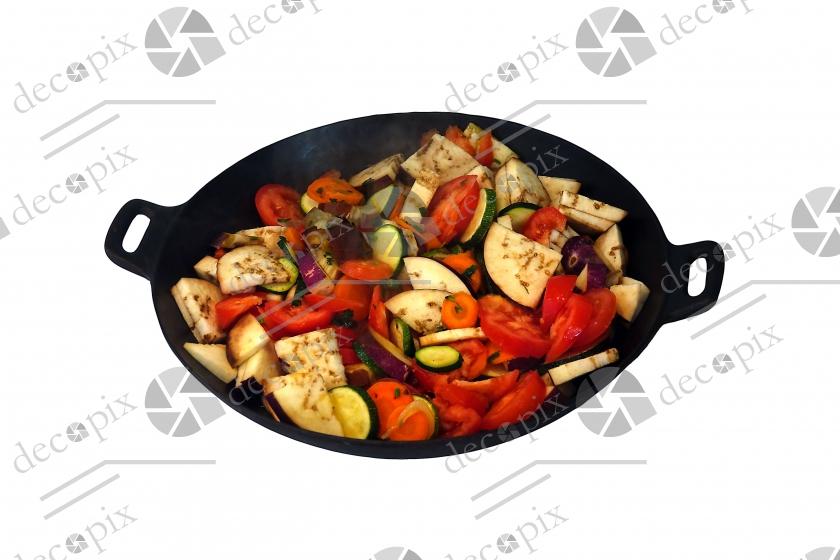 Wok contenant des légumes crus sur fond blanc