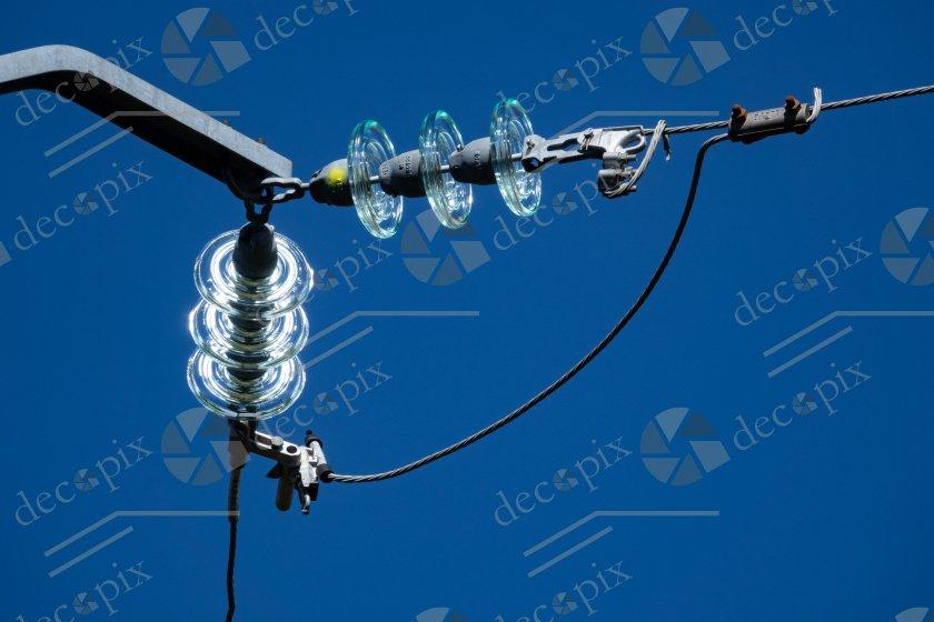 Fils et isolateurs électriques se détachant sur le ciel