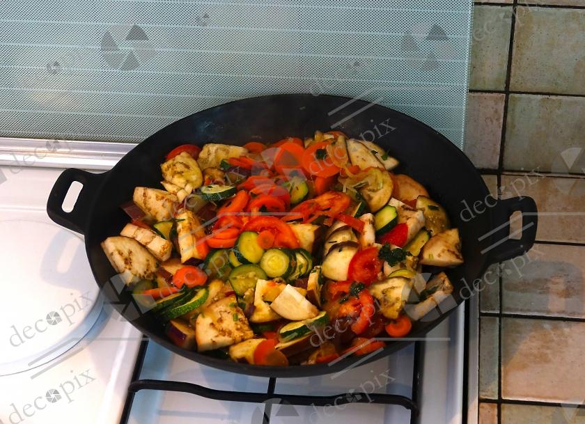 Wok sur cuisinière contenant des légumes crus