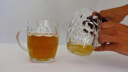 Gros plan sur les mains d'un homme versant de la bière dans une chope avant de trinquer
