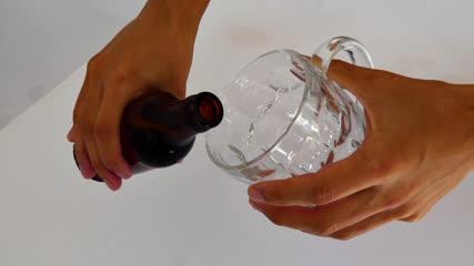 Gros plan sur les mains d'un homme versant de la bière dans une chope